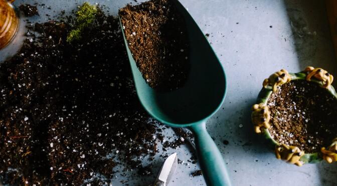 Een schepje met aarde gebruikt voor tuinonderhoud